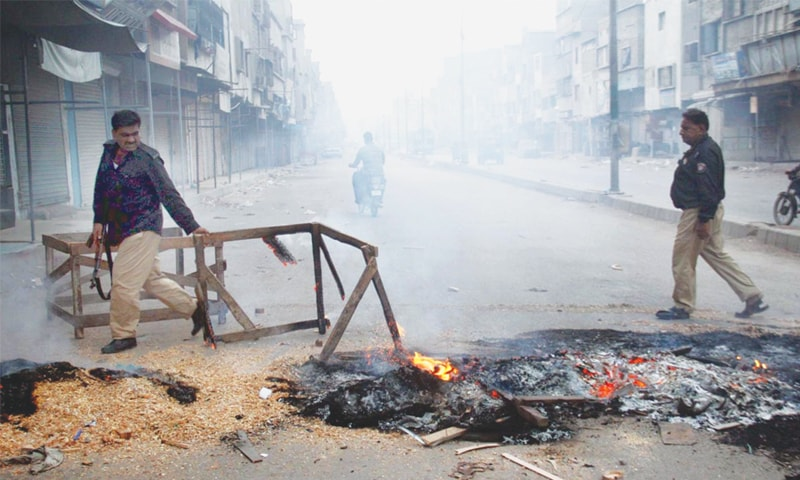 KARACHI: Policemen remove burning obstacles placed by protesters on a road on Tuesday after a vast area of the city suffered a major power outage.—Online