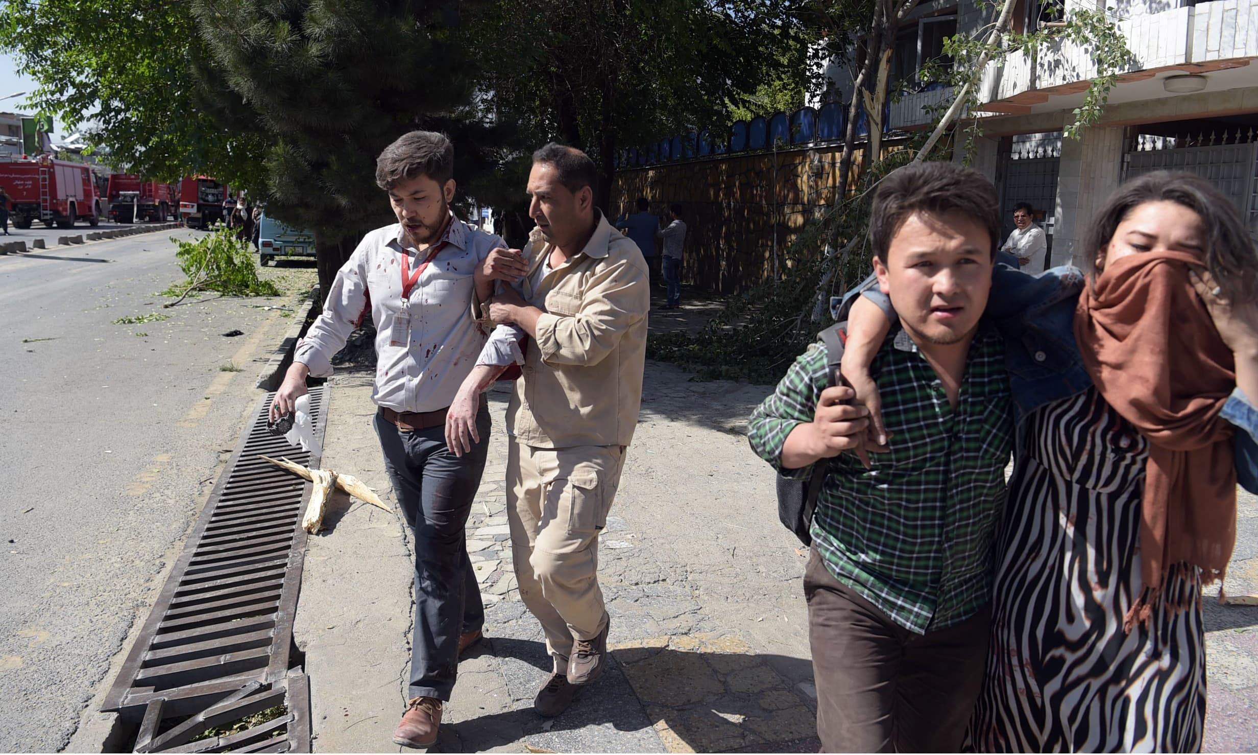 Afghan men provide assistance to the wounded at the site of a car bomb attack in Kabul. —AFP