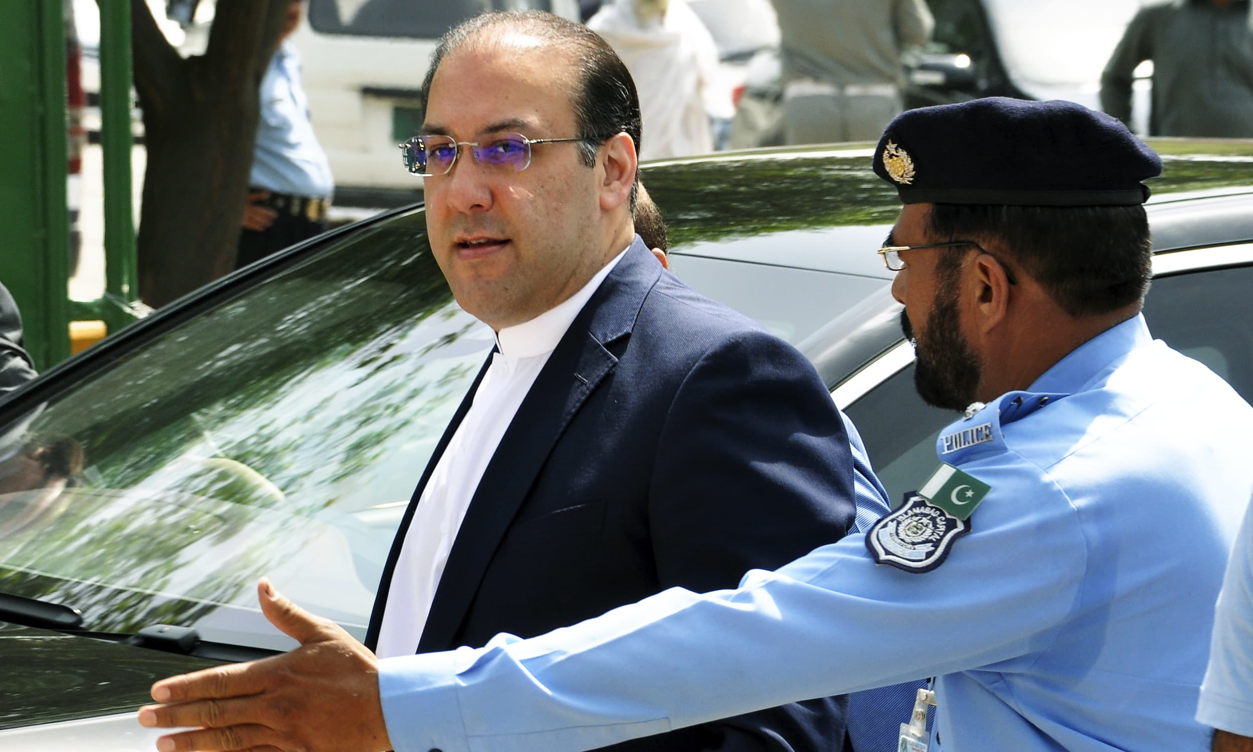 An official escorts Hassan Nawaz before his first appearance before the panel probing graft charges against his family. —AP