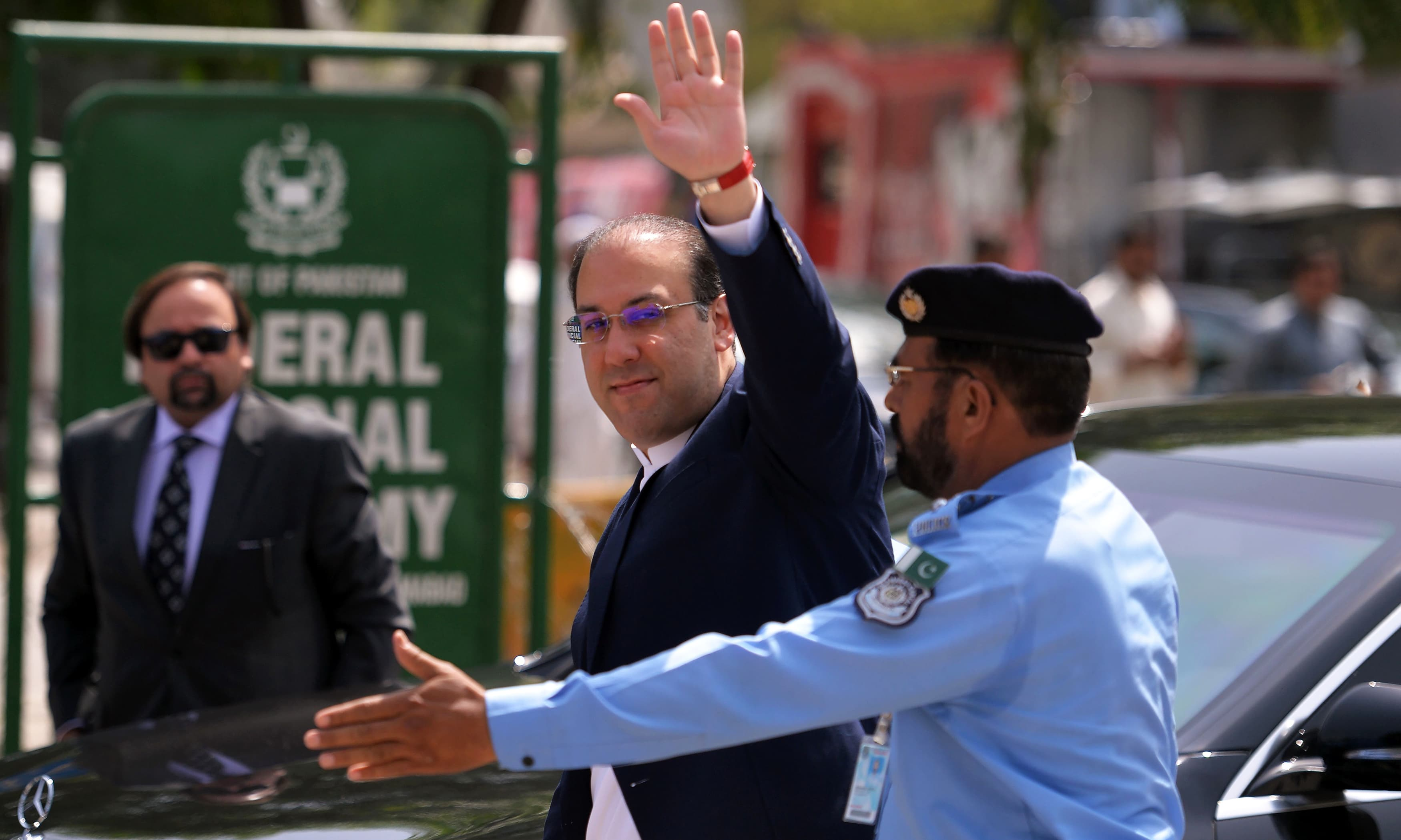 Hassan Nawaz waves as he arrives to record his statement before the JIT at the Federal Judicial Academy in Islamabad. —AFP