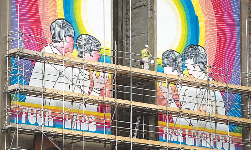 A mural by US artist Judy Chicago entitled 'Fixing a Hole', which depicts the Beatles and was inspired by their song of the same name from the Sgt Pepper's Lonely Hearts Club Band album, is pictured on the side of the disused White Tomkins & Courage Grain Silo in Stanley dock, Liverpool.—AFP