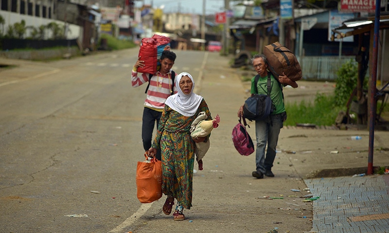 Residents carry their belongings as they walk along a deserted street as they flee from their homes in Marawi on June 3.— AFP