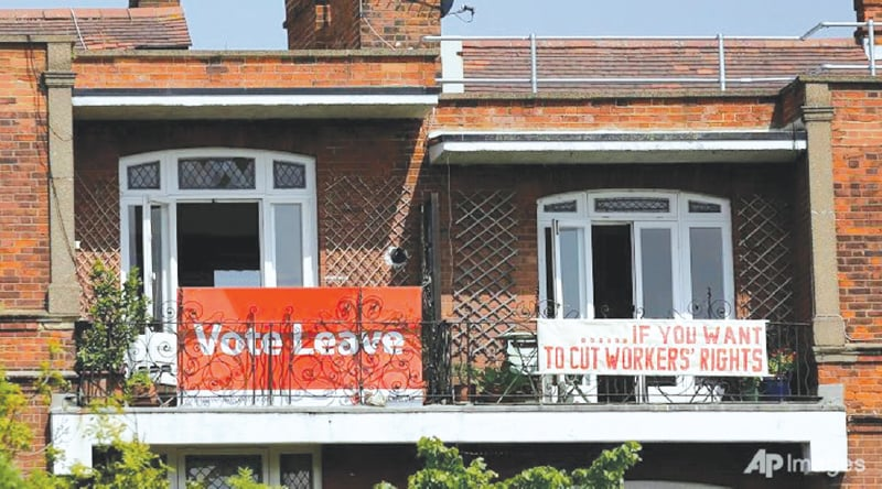 A country divided: a banner favouring Brexit is displayed outside a home adjacent to one that opposes Britain leaving the EU | AP