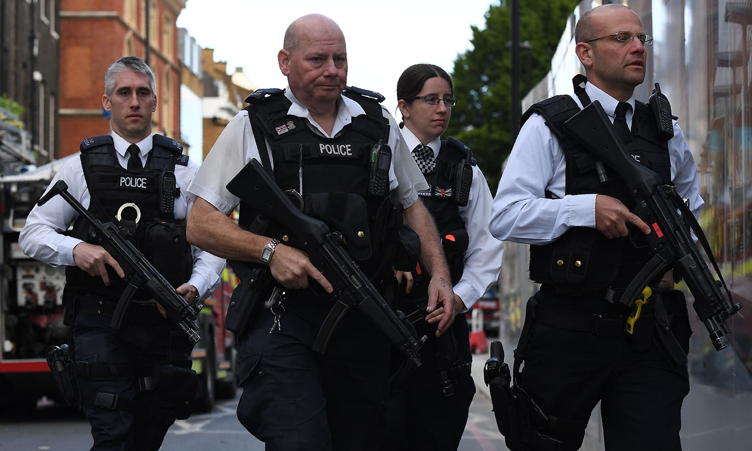 Armed police officers patrol the streets from Borough Market towards The Shard in London.─AFP