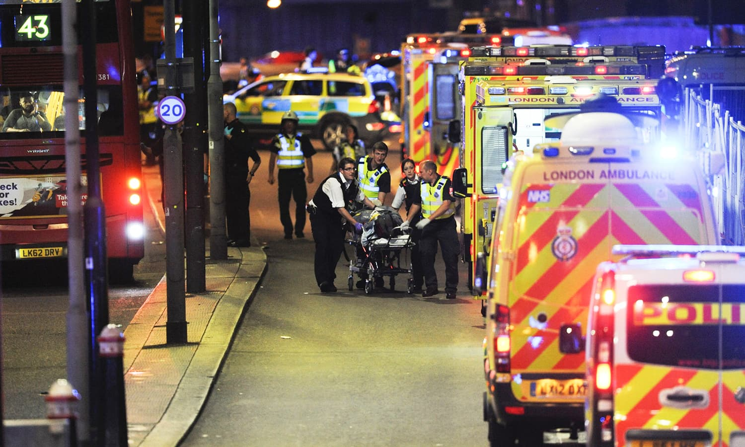 Police officers and members of the emergency services attend to a person injured in an apparent terror attack on London Bridge.─AFP