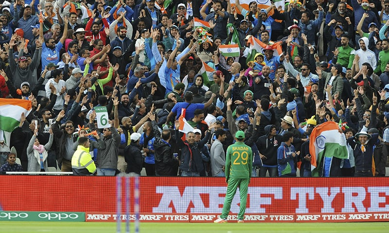 Shadab Khan stands by the boundary as Indian cricket fans cheer for their team.─AP