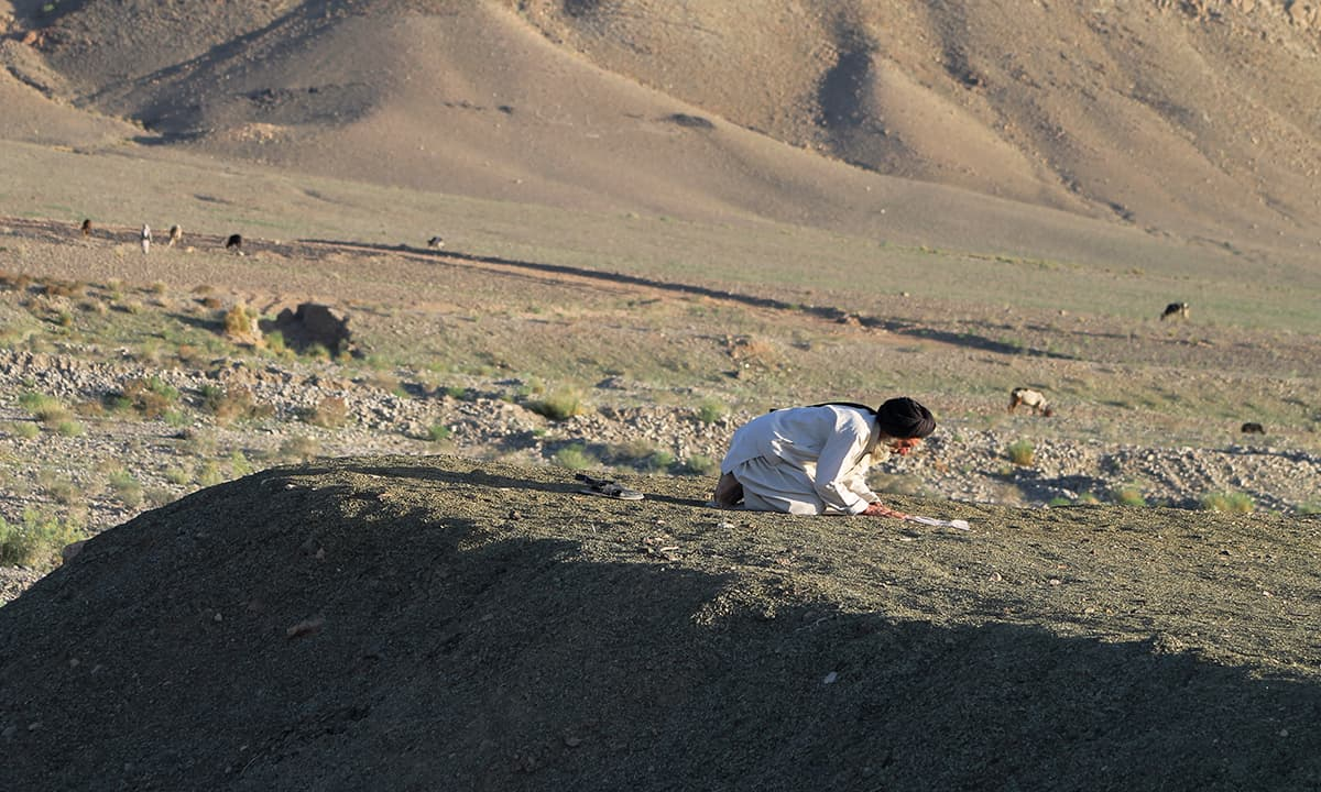 An elderly man offers prayers along the Zhob-Quetta Highway in Killa Saifullah district