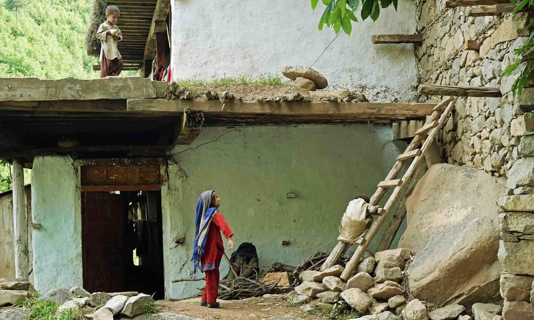 برابڑو بانڈہ کے ایک گھر میں بچے کھیل رہے ہیں— تصویر امجد علی سحاب