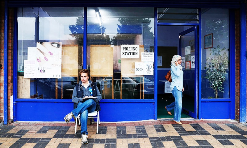 A woman leaves a polling station set up in a launderette and nail bar in Headington outside Oxford, west of London.—AFP