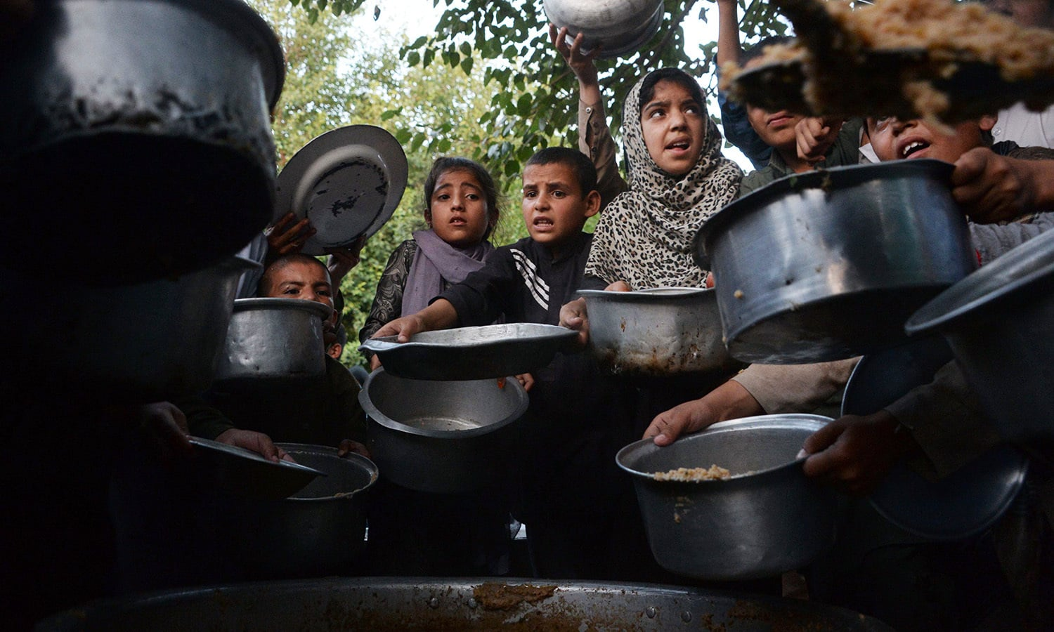 Afghan children hold dishes as they wait to receive food donated by a private charity in Jalalabad.— AFP