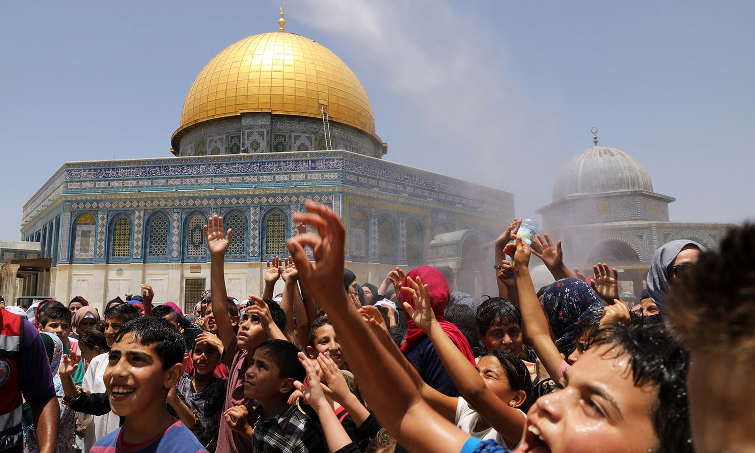 Muslims enjoy water spray over the crowd to cool off during the Friday prayers at the compound known to Muslims as Noble Sanctuary and to Jews as Temple Mount, in Jerusalem's Old City June 9.— Reuters