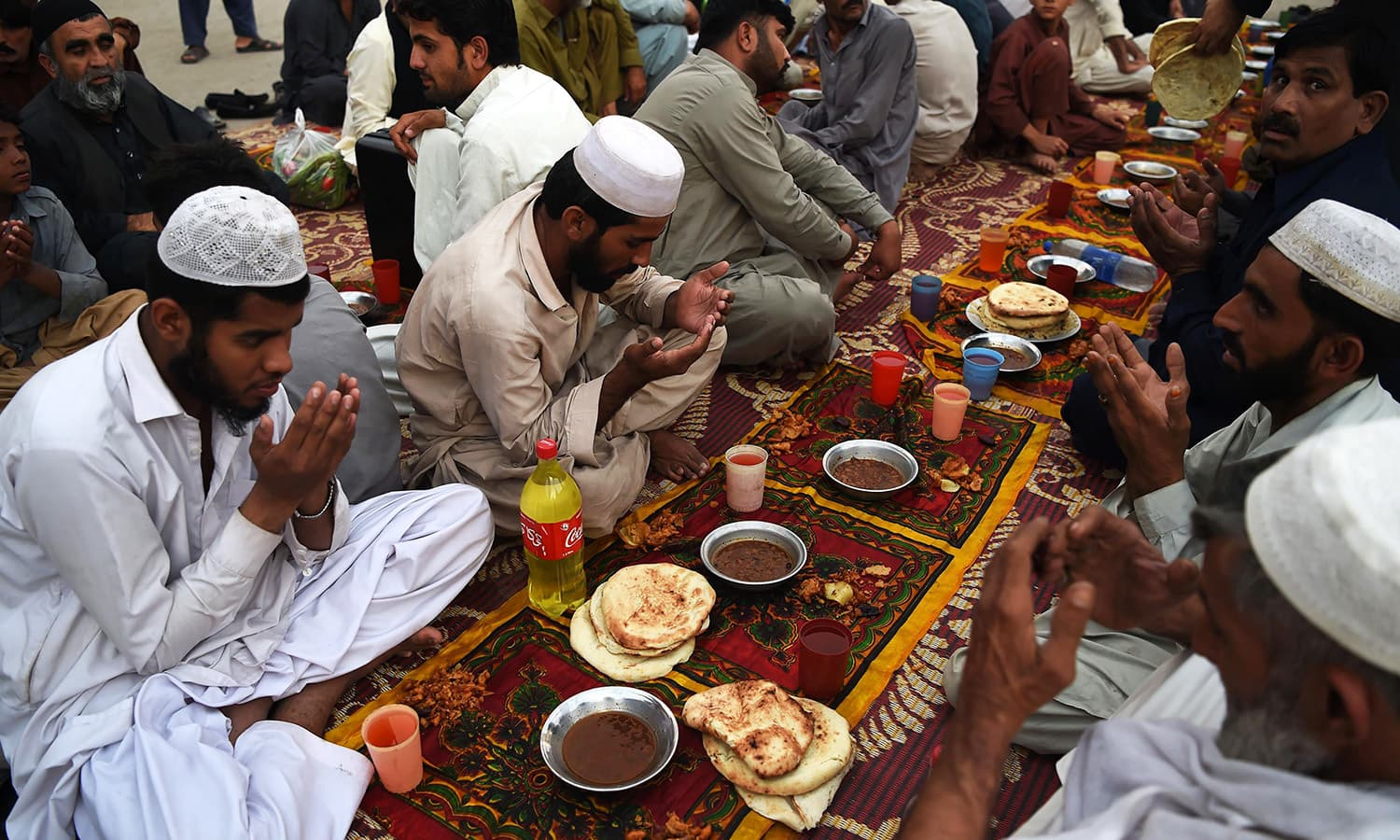 Pakistani residents offer prayers before breaking their fast in Peshawar on June 8. — AFP