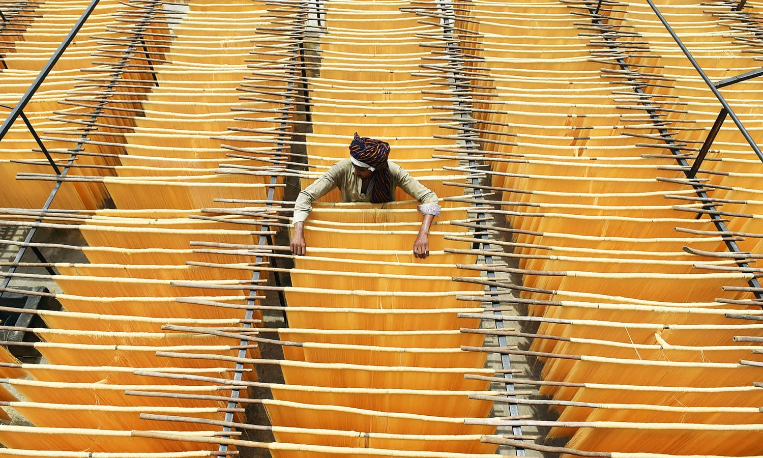 A man dries Seviiyan (thin vermicelli) at a factory in Lahore on June 8.— AFP