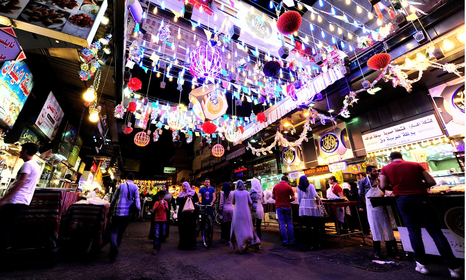 People walk as they shop along a decorated street during Ramazan in Damascus, Syria June 8.— Reuters