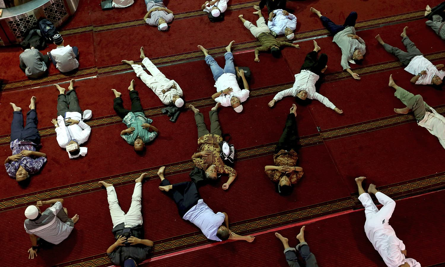 Muslim men nap as they wait for the time to break their fast after Friday prayer at the Istiqlal Mosque in Jakarta, Indonesia.— AP