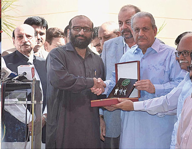 ACTING President Mian Raza Rabbani hands over keys of ambulances presented by the Senate of Pakistan to Faisal Edhi outside the Sindh Assembly on Saturday.—APP