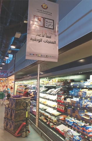 "DOHA: Customers at Al Meera market on Saturday. The writing in Arabic reads  ""Let's support national products"".—AFP"