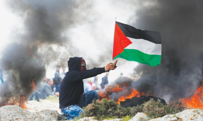March 24, 2017: A protester holds aloft a Palestinian flag in the midst of clashes at a protest against new Jewish settlements in Mughayer village near the West Bank city of Ramallah | Nasser Shiyoukhi/ AP file photo