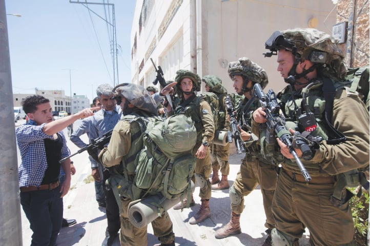 June 15, 2014: A Palestinian youth argues with Israeli soldiers as he tries to enter his home during a military operation to search for three missing teenagers outside the city of Hebron. Israeli troops arrested some 80 Palestinians from the village after PM Benjamin Netanyahu accused Hamas of kidnapping the three teenagers | Majdi Mohammed/AP file photo