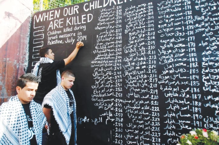 July, 2014: Young Palestinians list the names of the children who were killed in yet another Israeli military assault on the Gaza Strip | Musa Al Shaer/ AFP file photo