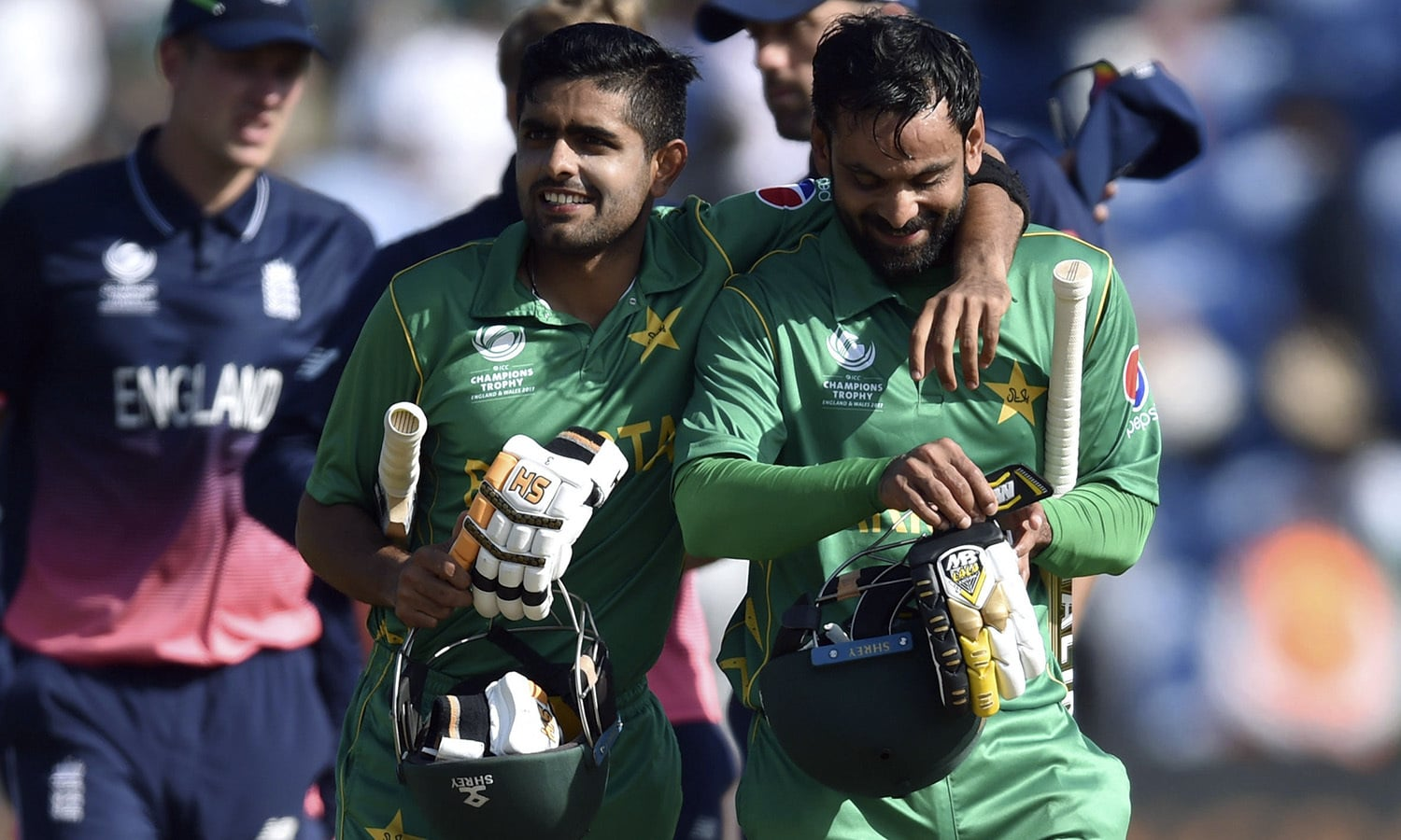 Babar Azam and Mohammad Hafeez, right, celebrate victory as they leave the pitch.— AP