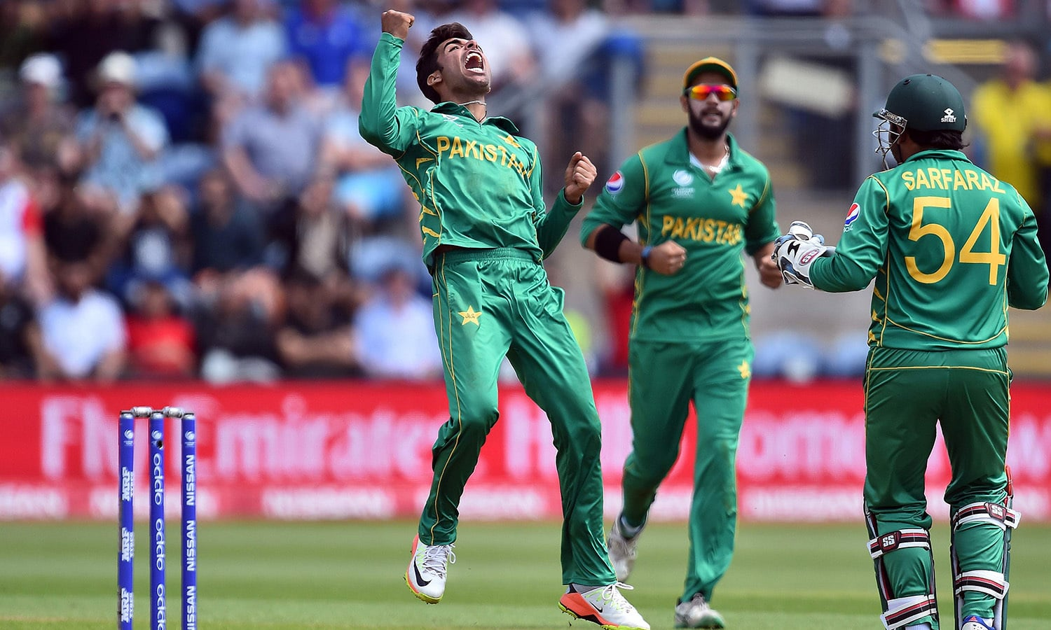 Shadab Khan (L) jumps in jubilation after taking the wicket of Joe Root (unseen) for 46 runs.─AFP