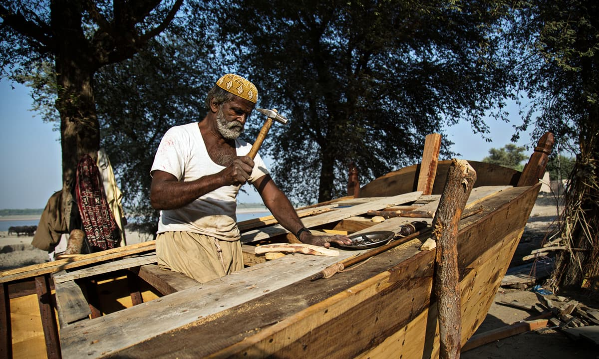 A fisherman works on building a boat in Sann, Sindh