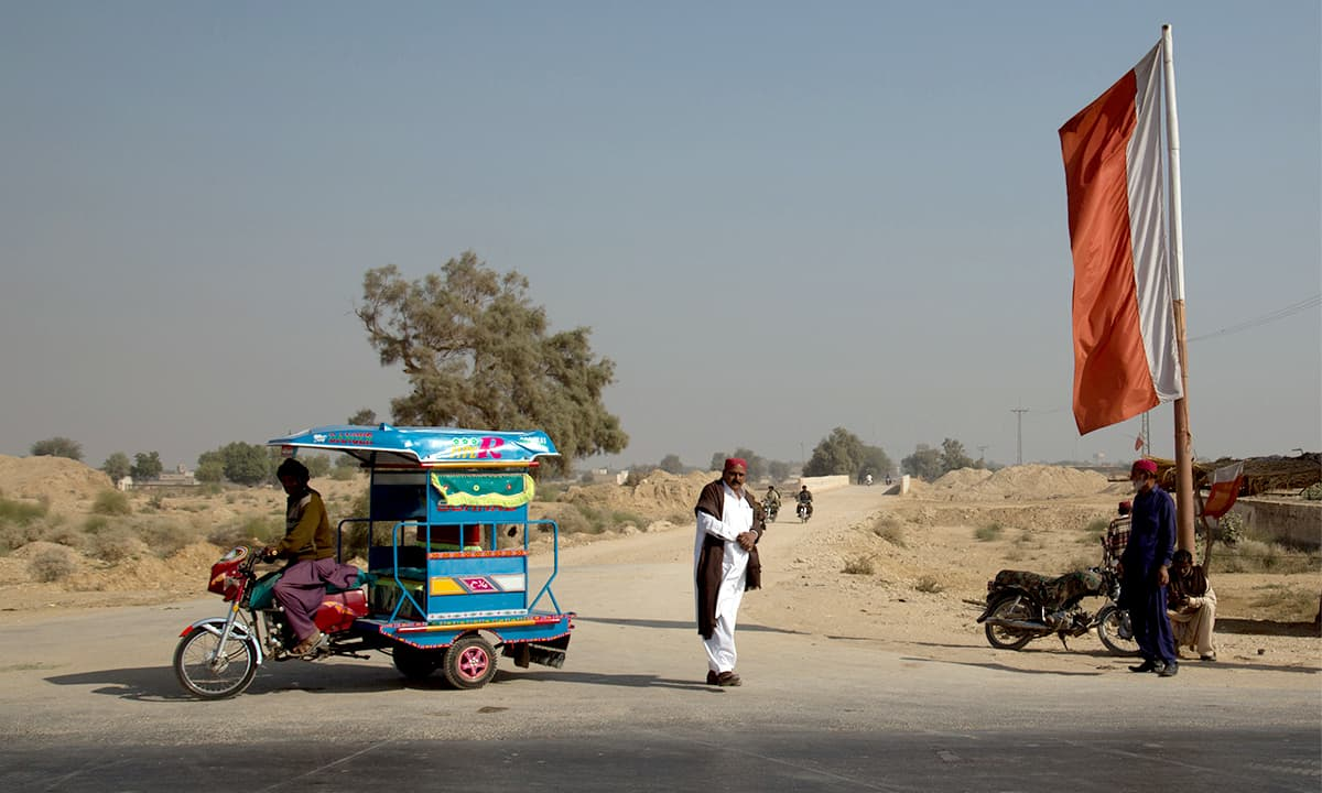 A flag representing the Sindh United Party (SUP) at a road crossing near Sann