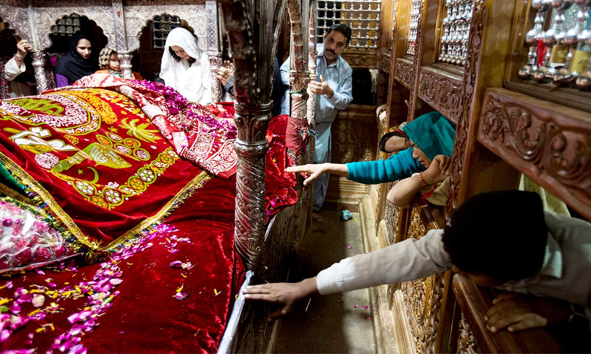 Pilgrims touch Lal Shahbaz Qalandar's grave through a fence