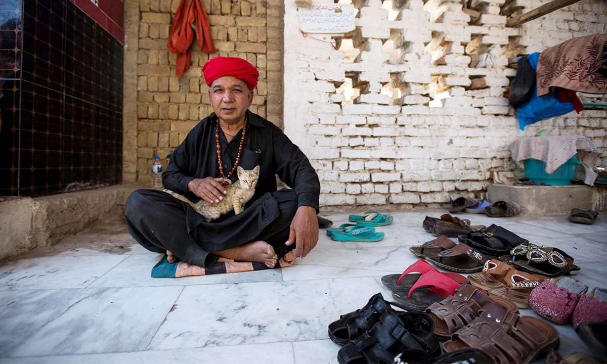 Zamir Hussain sits outside the shrine of Bodla Sikandar who was one of Lal Shahbaz Qalandar's companions