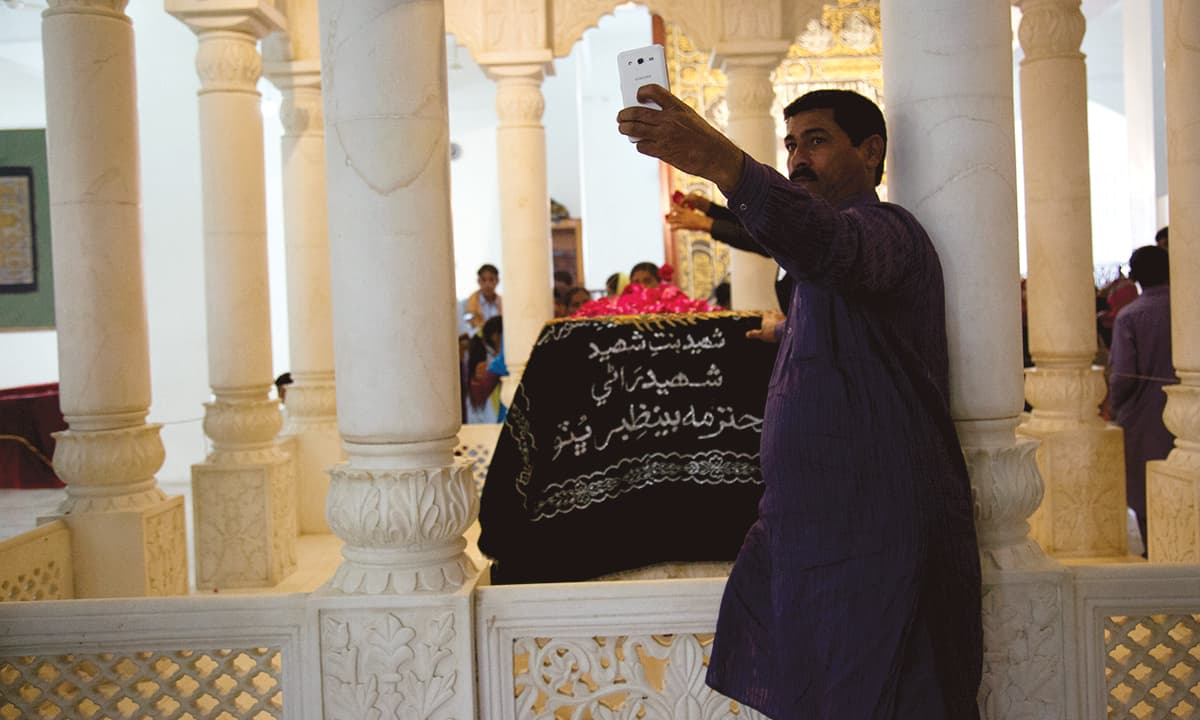A visitor takes a selfie with the grave of Benazir Bhutto in Garhi Khuda Bakhsh