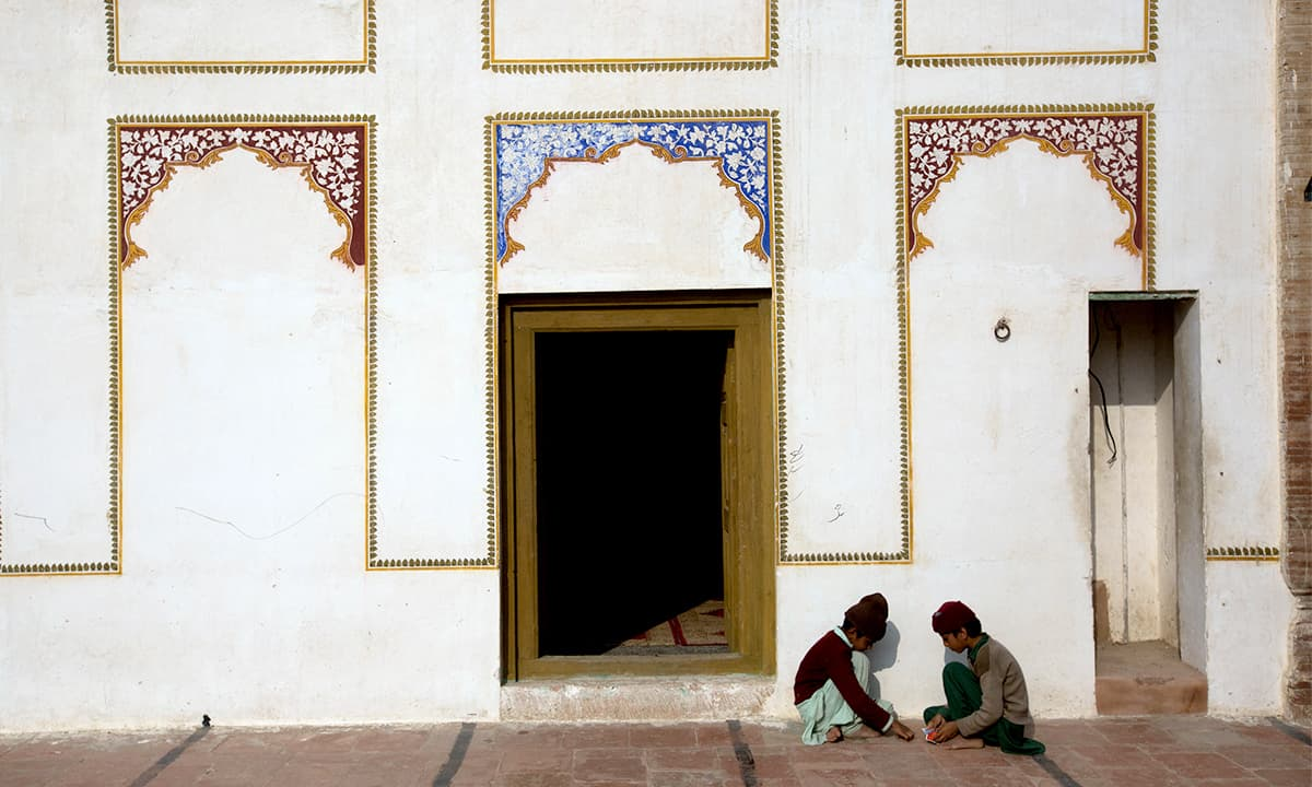 Two friends play outside the shrine of Khawaja Ghulam Farid