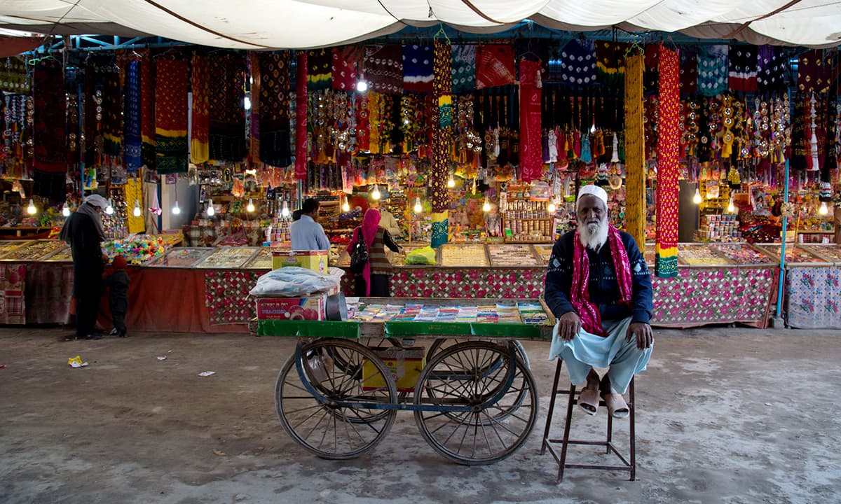 An elderly man sits next to his cart in a market outside the shrine of Khawaja Ghulam Farid