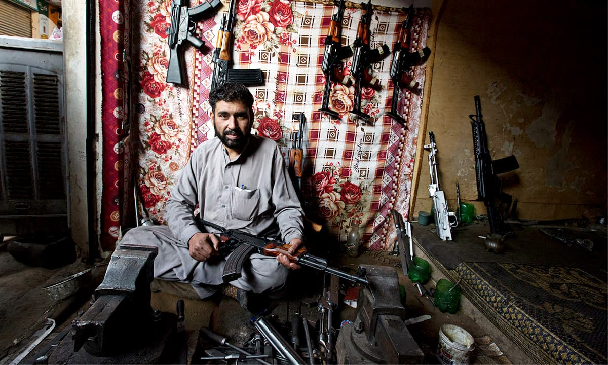 Bismillah Jan sits with his guns in his shop in Darra Adam Khel