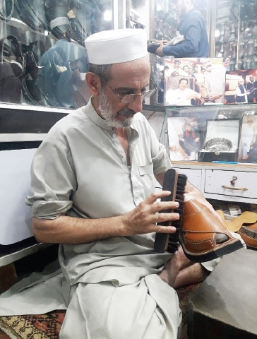 A cobbler gives final touches to Peshawari chappal at his workplace. — Dawn