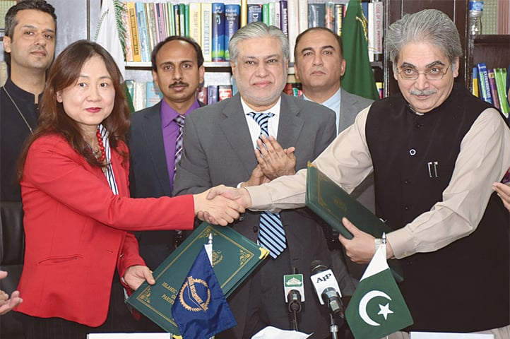 ISLAMABAD: Economic Affairs Division Secretary Tariq Mahmood Pasha and Asian Development Bank's Country Director Xiaohong Yang shake hands after signing a loan agreement between Pakistan and the bank to finance the Sustainable Energy Sector Reform Programme. Finance Minister Senator Ishaq Dar was also present at the event on Friday.—Online