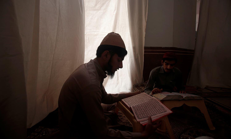 ایک نوجوان قرآن شریف کی تلاوت کرنے میں مصروف ہے — فوٹو/ رائٹرز