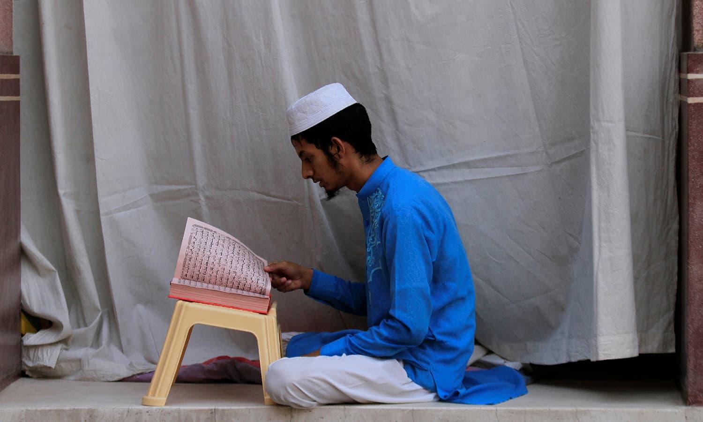 ایک شخص پشاور کی ایک مسجد میں اعتکاف میں بیٹھنے کے بعد قرآن مجید کی تلاوت کررہا ہے — فوٹو/ رائٹرز