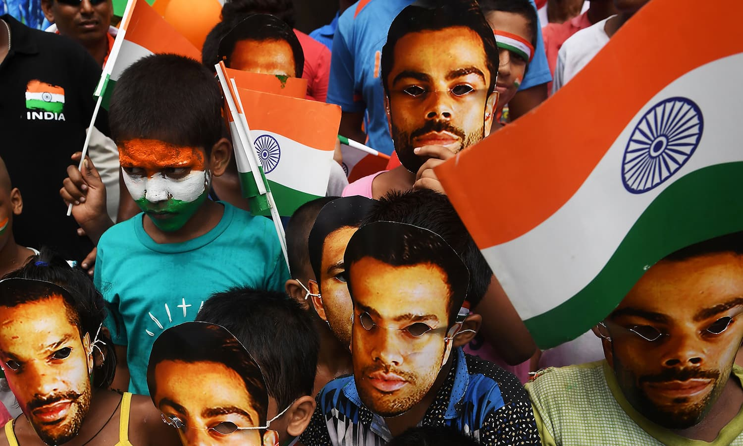 Young Indian cricket fans wear masks of the face of India's captain Virat Kohli and others in Kolkata on June 18.─AFP