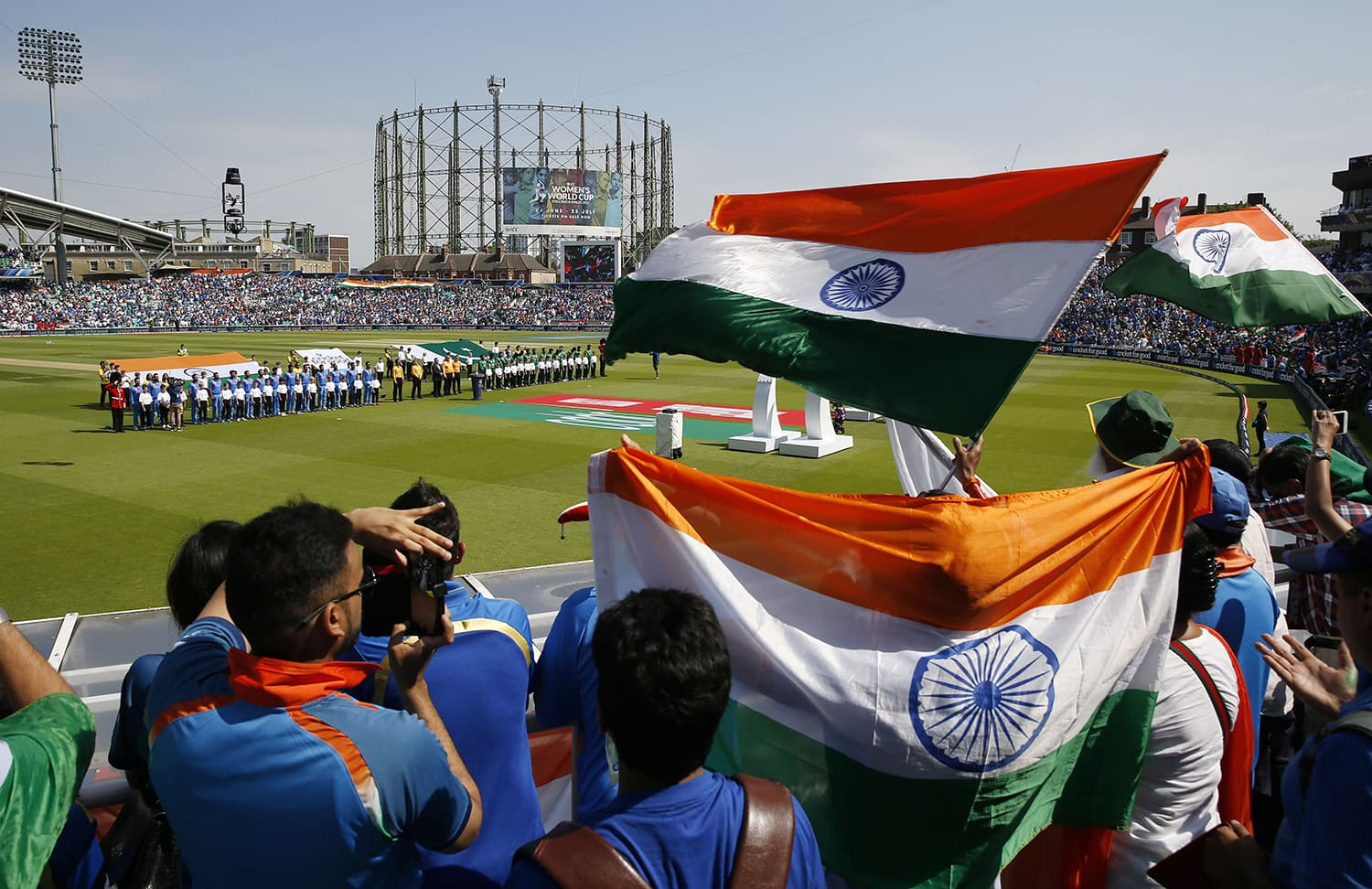 India and Pakistan fans wave flags as the players line up before the match.─Reuters