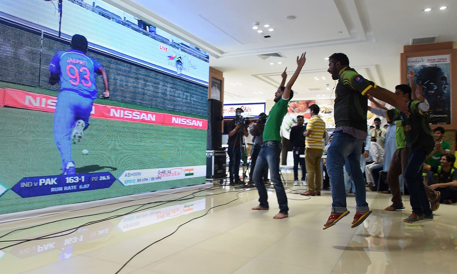 Pakistani cricket fans celebrate as they watch the cricket final match between Pakistan and India at a shopping mall in Lahore on June 18.─AFP