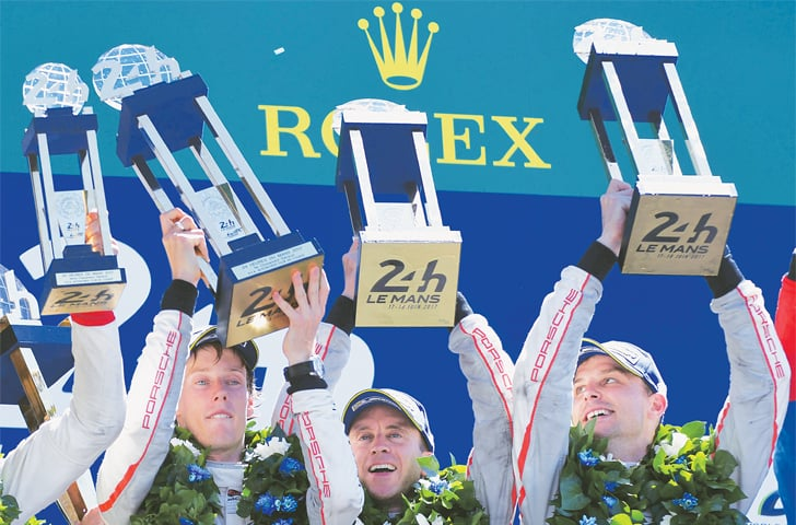 LE MANS (France): (LtoR) New Zealand's drivers Brendon Hartley, Earl Bamber and Germany's driver Timo Bernhard celebrate with their trophies on the podium after winning the 85th Le Mans 24-hour endurance race on Sunday.—AFP