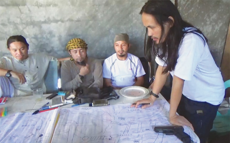 THIS screen grab taken from a handout video released by the Philippine Army on Sunday shows Abdullah Maute (right) looking at an improvised map of Marawi, while Isnilon Hapilon (second left), leader of hard-line group Abu Sayyaf, looks on, as they plan an attack on Marawi city at an undisclosed location on Mindanao island.—AFP