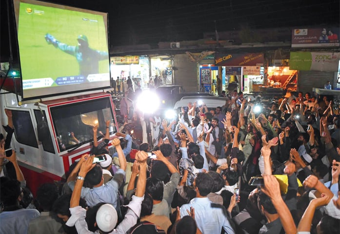 Jubilant youth celebrate Pakistan victory while watching Champions Trophy cricket final on a big screen at Qayyum Stadium Chowk, Peshawar, on Sunday. — Photo by Shahbaz Butt