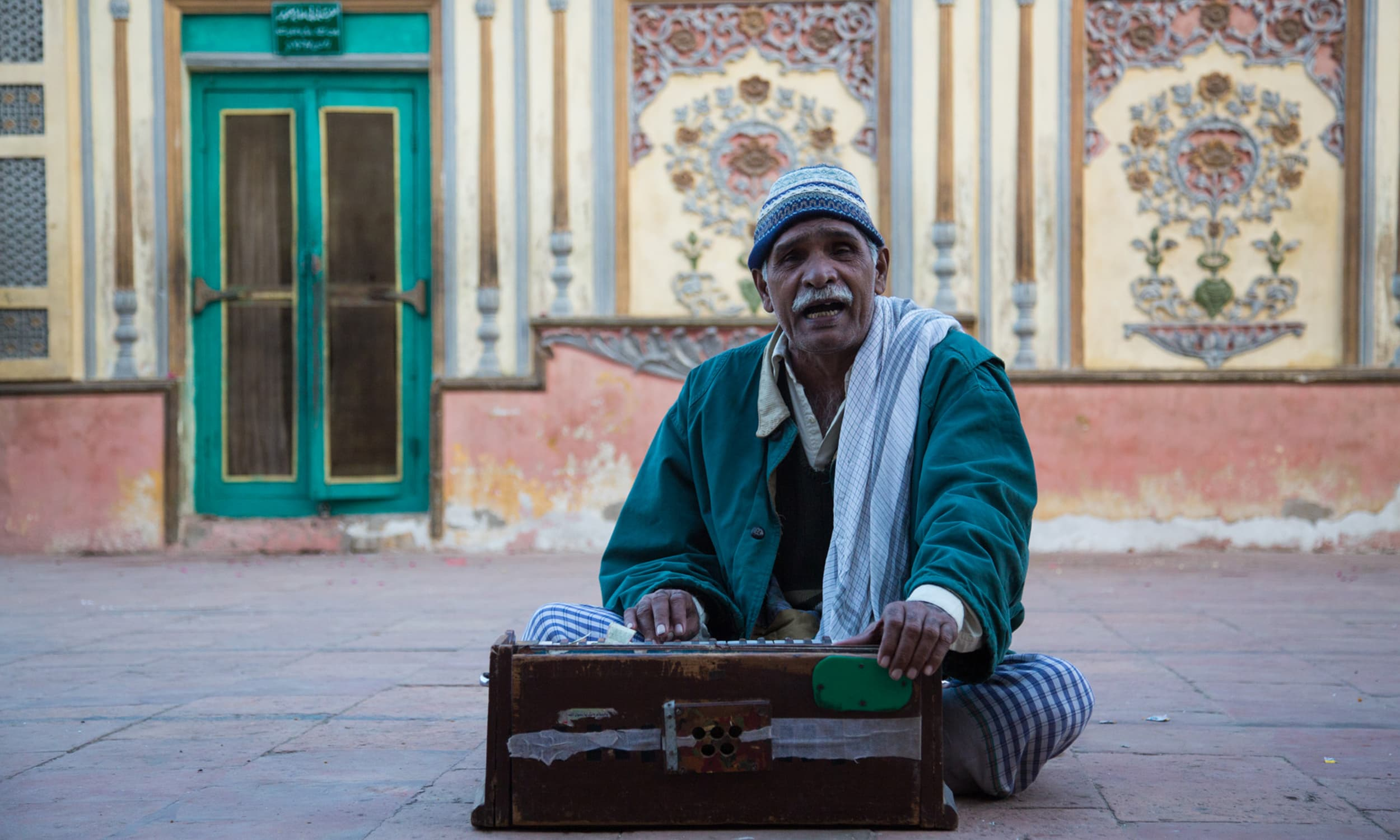 A man plays the harmonium and sings inside the shrine of Khawaja Ghulam Farid