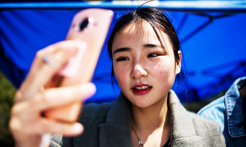 This picture shows Jiang Mengna live broadcasting during a break at the Yiwu Industrial and Commercial College in Yiwu, east China's Zhejiang Province. —AFP