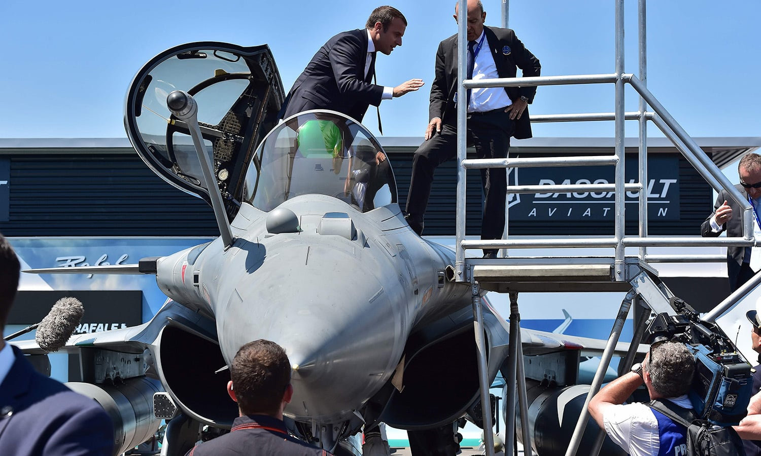 France's President Emmanuel Macron (top, L) exits a Dassault Aviation Rafale fighter jet as Dassault Aviation CEO Eric Trappier (top, R) looks on. ─ AFP