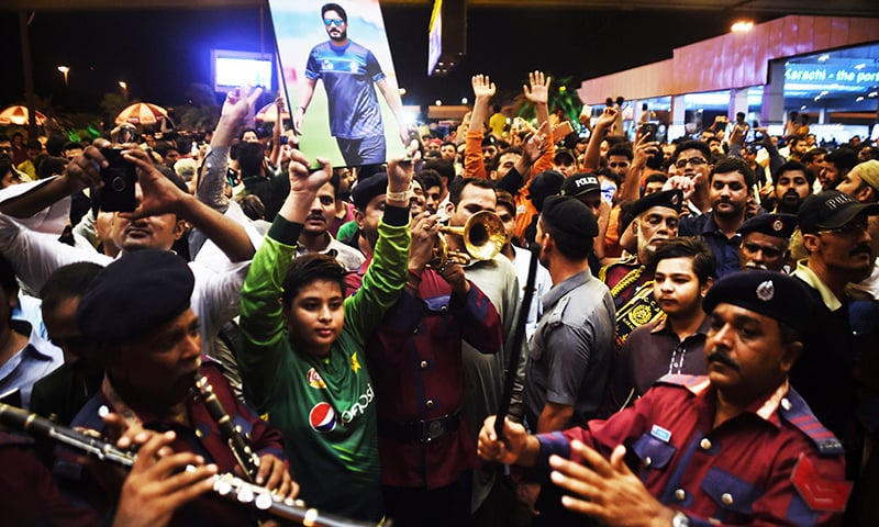 Fans gather outside the Karachi International airport to welcome their national team's arrival from London in Karachi.─AFP