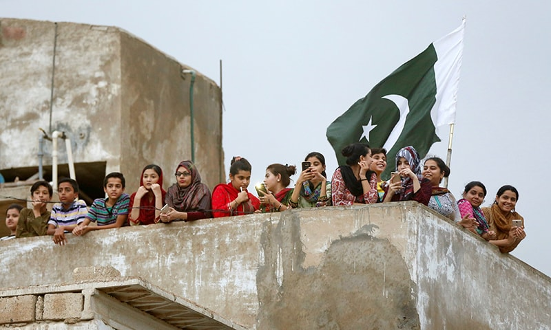 Women and children gather on a roof as they watch the arrival of Sarfraz Ahmed to his house after winning the ICC Champions Trophy.─Reuters
