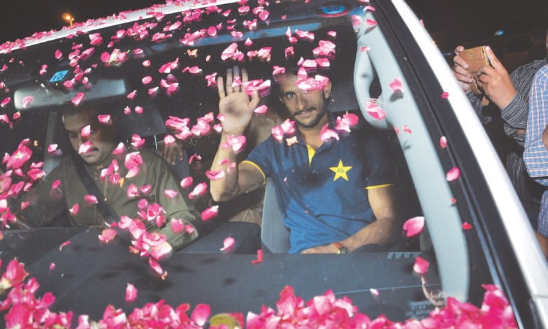 LAHORE: Pace bowler Hasan Ali waves to his fans who showered rose petals on his car at the Allama Iqbal International Airport upon his arrival here on Tuesday.—AP